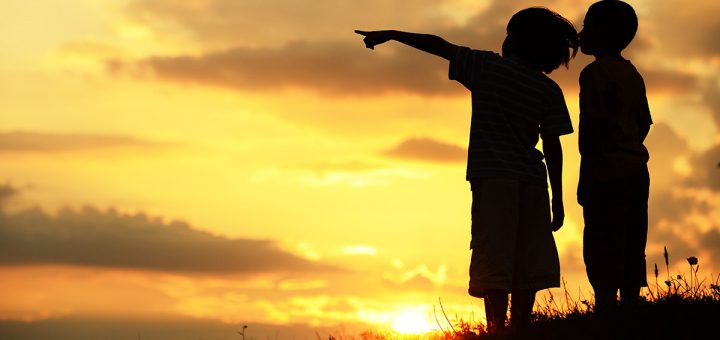 Children pointing to the future at sunset